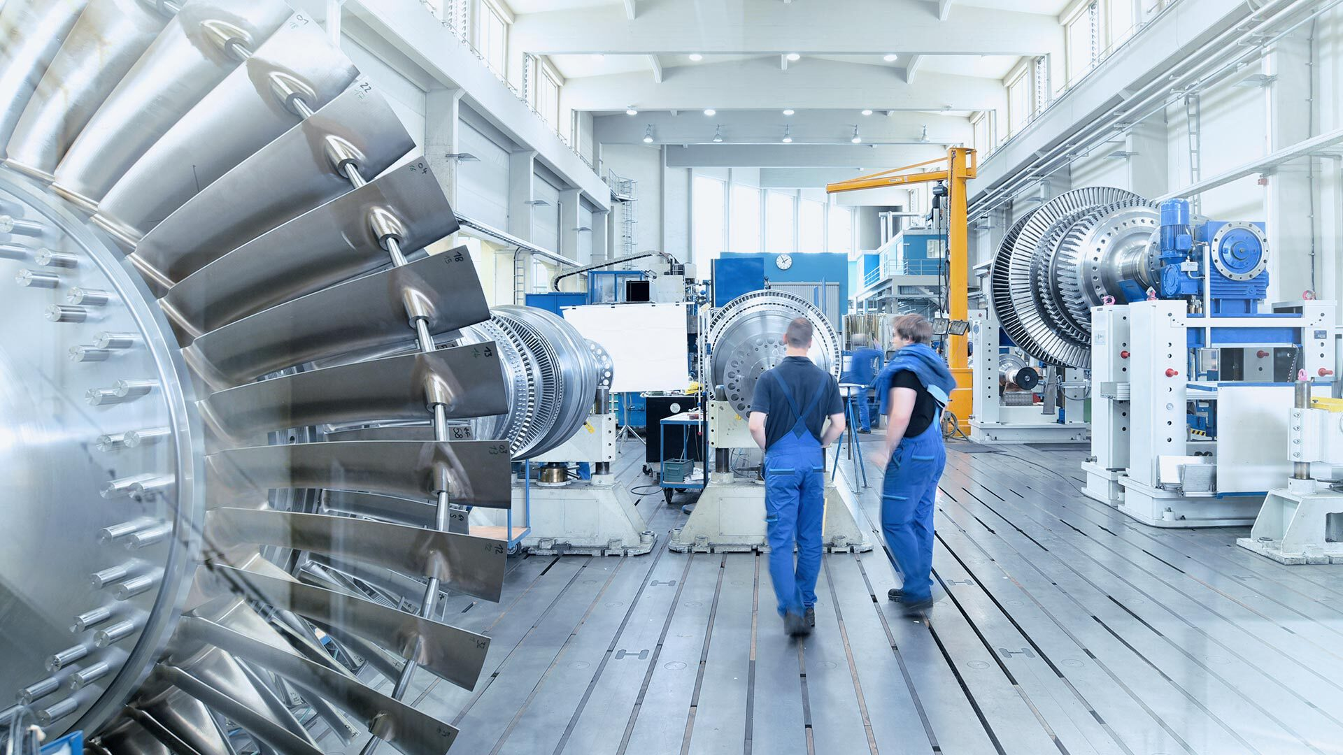 two engineers are walking through an industrial hall with machinery